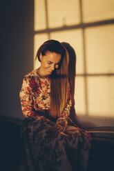 Smiling young woman in sunlight in a room - MAUF000126