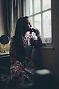 Young woman in floral dress looking out of window - MAUF000129