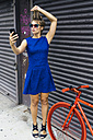 Portrait of blond woman wearing blue summer dress taking a selfie with smartphone - GIOF000554