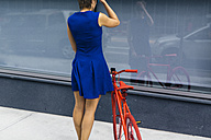 Back view of woman wearing blue summer dress looking at her reflection on a glass pane - GIOF000557