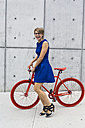 Happy blond woman with red racing cycle - GIOF000563