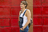 Smiling blond woman wearing jeans dungarees in front of red background - GIOF000566