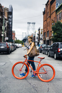 USA, New York City, Williamsburg,  woman withg red racing cycle crossing the street - GIOF000578