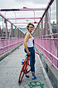 USA, New York City, Williamsburg,  smiling woman with red racing cycle on Williamsburg Bridge - GIOF000581