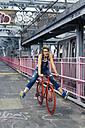 USA, New York City, Williamsburg,  woman with red racing cycle on Williamsburg Bridge - GIOF000584