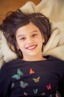 Portrait of smiling girl lying on blanket on the floor - LVF004229