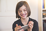 Portrait of smiling girl looking at smartphone - LVF004232