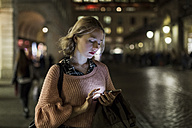 UK, London, young woman using smartphone on the street in the evening - MAUF000133