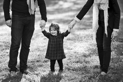 Mother and father holding hands of smiling baby girl - LITF000067