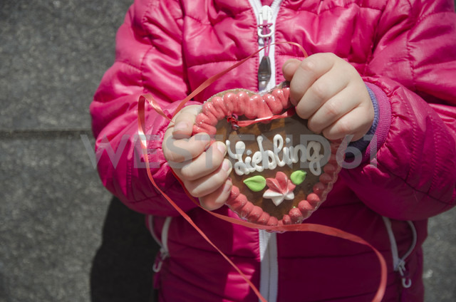 Girl holding gingerbread heart with German inscription - GSF001013