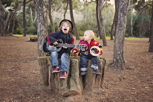 Little boy playing guitar and singing for his baby brother in a forest - LITF000083