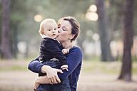 Mother holding baby boy in her arms and kissing him on the cheek - LITF000086