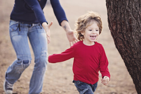 Smiling toddler being chased by his Mom - LITF000092