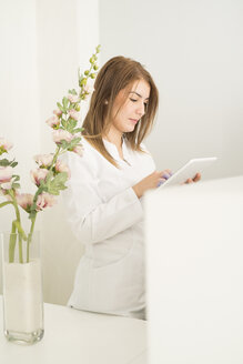 Young woman at reception in clinic using digital tablet - JASF000275