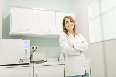 Portrait of smiling health professional next to autoclave machine in clinic lab - JASF000281