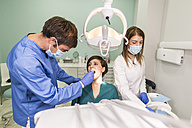 Dentist and his assistant examining the teeth of a patient - JASF000290