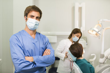 Portrait of dentist wearing mask with assistant and patient in background - JASF000302