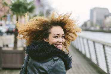 Ireland, Dublin, smiling woman with afro looking over her shoulder - BOYF000028