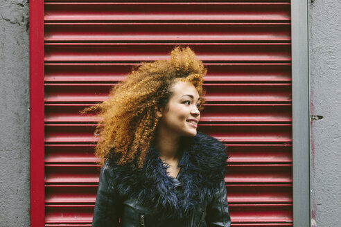 Ireland, Dublin, smiling woman with afro in front of red roller shutter - BOYF000031