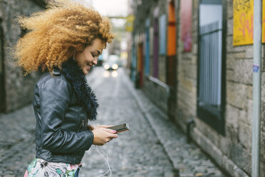 Ireland, Dublin, smiling woman with afro looking at her smartphone - BOYF000034