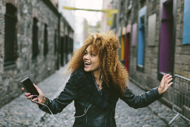 Ireland, Dublin, happy woman with afro hearing music with smartphone and earphones - BOYF000037