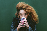 Portrait of woman drinking coffee to go in front of a green wall - BOYF000043