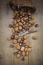 Wickerbasket, walnuts, almonds, hazelnuts and nutcracker on wood - LVF004256