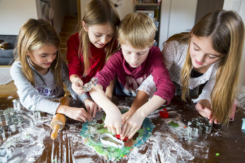Four children cutting out Christmas cookies at home - SARF002386