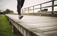 Spain, Naron, legs of a jogger running on a boardwalk - RAEF000698