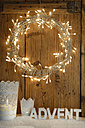 White decoration with lighted Advent wreath in front of wooden wall - LBF001307