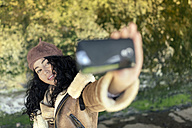 Woman outdoors taking a selfie - MGOF001133