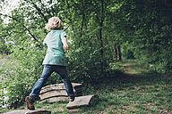 Germany, Saxony, boy running in the woods - MJF001679