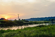 Germany, Saxony, river Mulde and power pylons at sunset - MJF001697