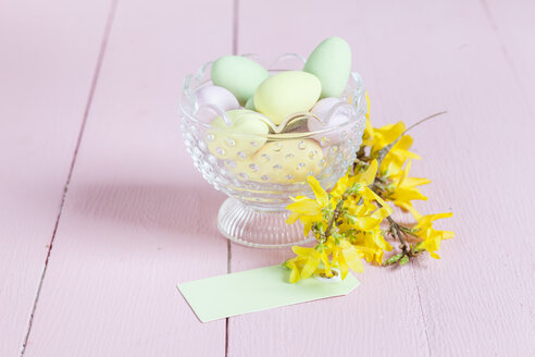 Glass bowl with sweet Easter eggs and Forsythia twig - SBDF002558