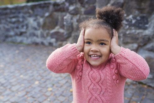 Little girl smiling, hands over ears - HAPF000020