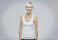 Portrait of happy blond woman wearing white top in front of grey background - RH001056