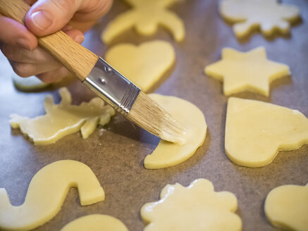 Woman spreading icing on raw Christmas cookies, close-up - KRPF001652