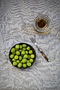 Bowl of green olives, fork  and carafe with olive oil - LVF004277
