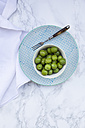 Bowl of green olives on plate and white marble - LVF004289