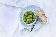 Bowl of green olives, fork and slices of bread on plate - LVF004292