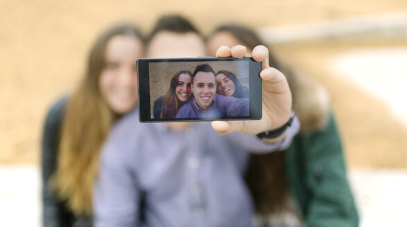 Selfie of smiling friends on display of smartphone - MGOF001138