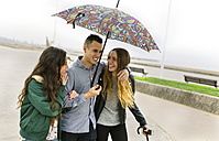 Three happy friends walking down the street with umbrella - MGOF001141
