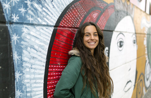 Portrait of smiling young woman at mural - MGO001147