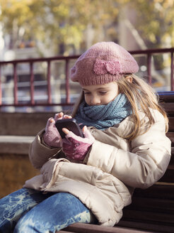 Girl in winter clothing playing with smartphone - XCF000042