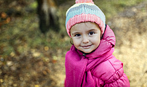 Portrait of smiling little girl wearing cap and scarf in autumn - MGOF001154
