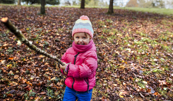 Portrait of happy little girl playing on a meadow in autumn - MGOF001160