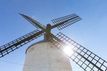 Spain, Consuegra, old windmill in front of blue sky at backlight - ERLF000087