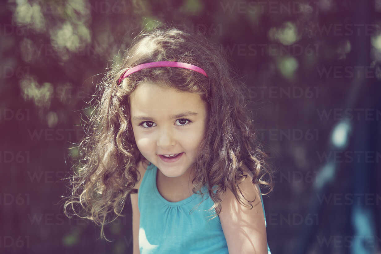 Portrait of smiling little girl with curly brown hair - ERLF000088 - Enrique Ramos/Westend61