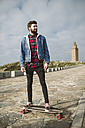 Young casual man standing on his longboard, lighthouse in background - RAEF000716