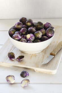 Red brussels sprouts in bowl, chopping board and knife - EVGF002542